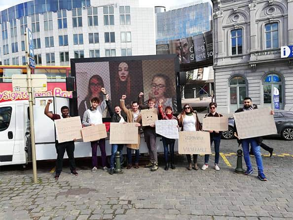 A picture of people holding signs in Brussels, Belgium. In support of the QUEEN and Films United In This Together campaign.